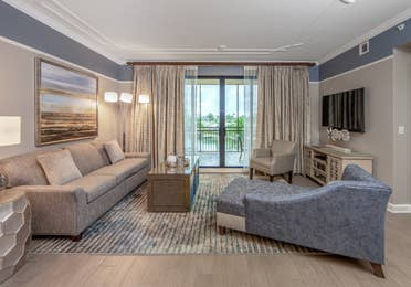 Living room with couch, two accent chairs, and flat screen TV with access to furnished balcony in a three-bedroom villa at Sunset Cove Resort in Marco Island, Florida