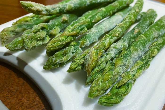Frozen asparagus sits on a white plate.