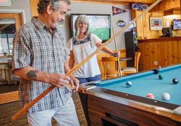 Two guests playing billiards in the Beartree Bar at Oak n' Spruce Resort in South Lee, Massachusetts.