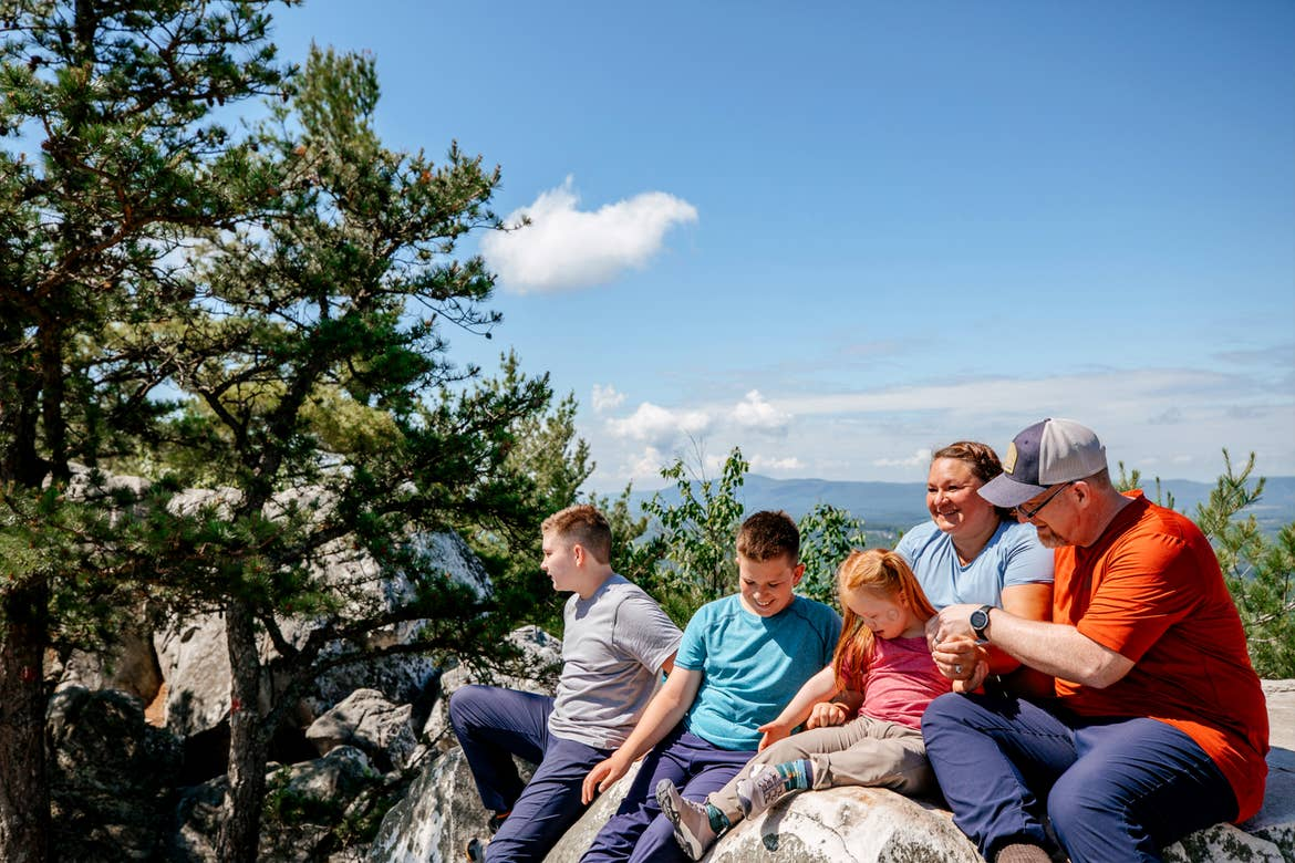 A caucasian family of five (left to right: Two tween boys, a young girl, a woman and man) sit on a rock formation near pine trees at the peak of Monument Mountain in Lee, Massachusetts.