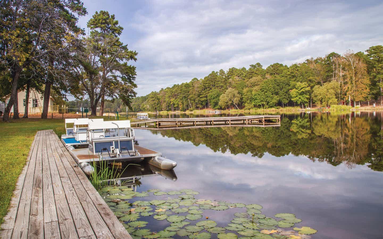 Boats at a dock on a lake at Holly Lake Resort in Texas.