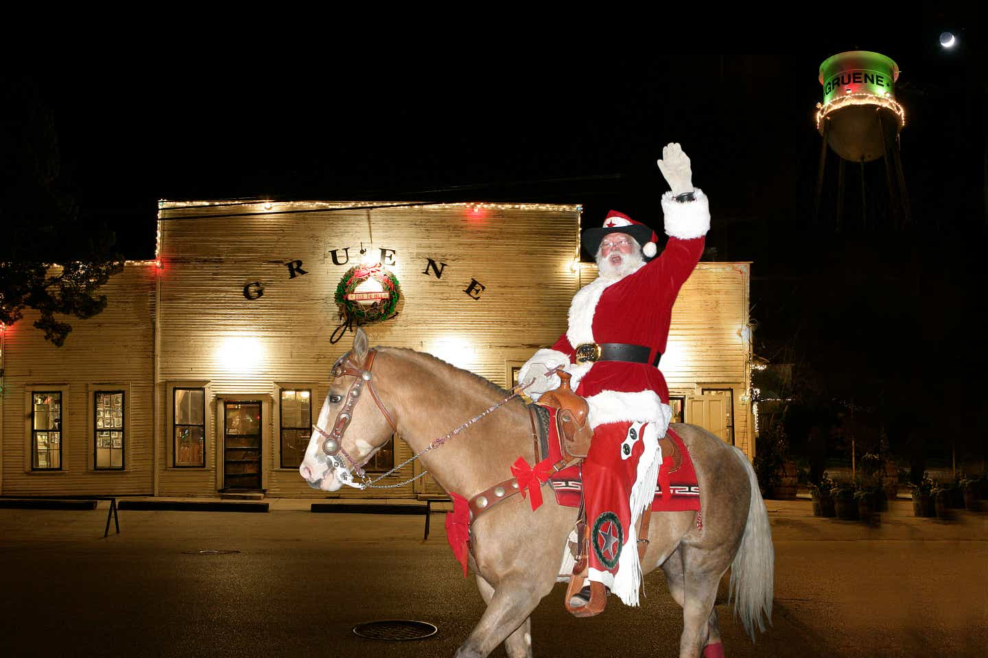 Cowboy Kringle wears a cowboy hat and red suit while riding a horse and waving to guests.