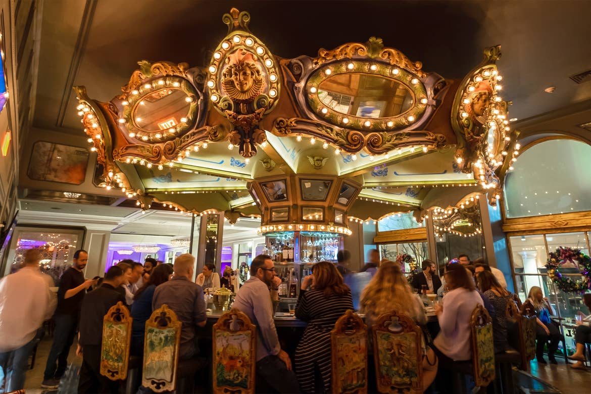 A carousel topper illuminated with rounded light bulbs is anchored above a rounded bar surrounded by patrons.