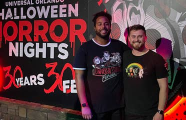 Two men wearing black t-shirts and shorts stand in front of a mural at night.
