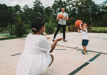 Family with two adults and small child playing basketball at Williamsburg Resort.