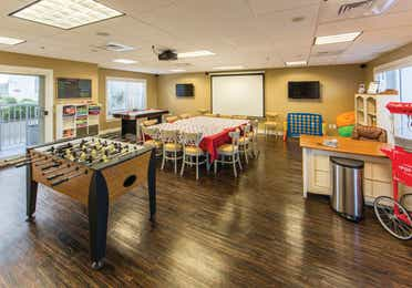 Game room with Foosball table, giant Connect 4, popcorn machine, and seating area in front of projector at Galveston Beach Resort