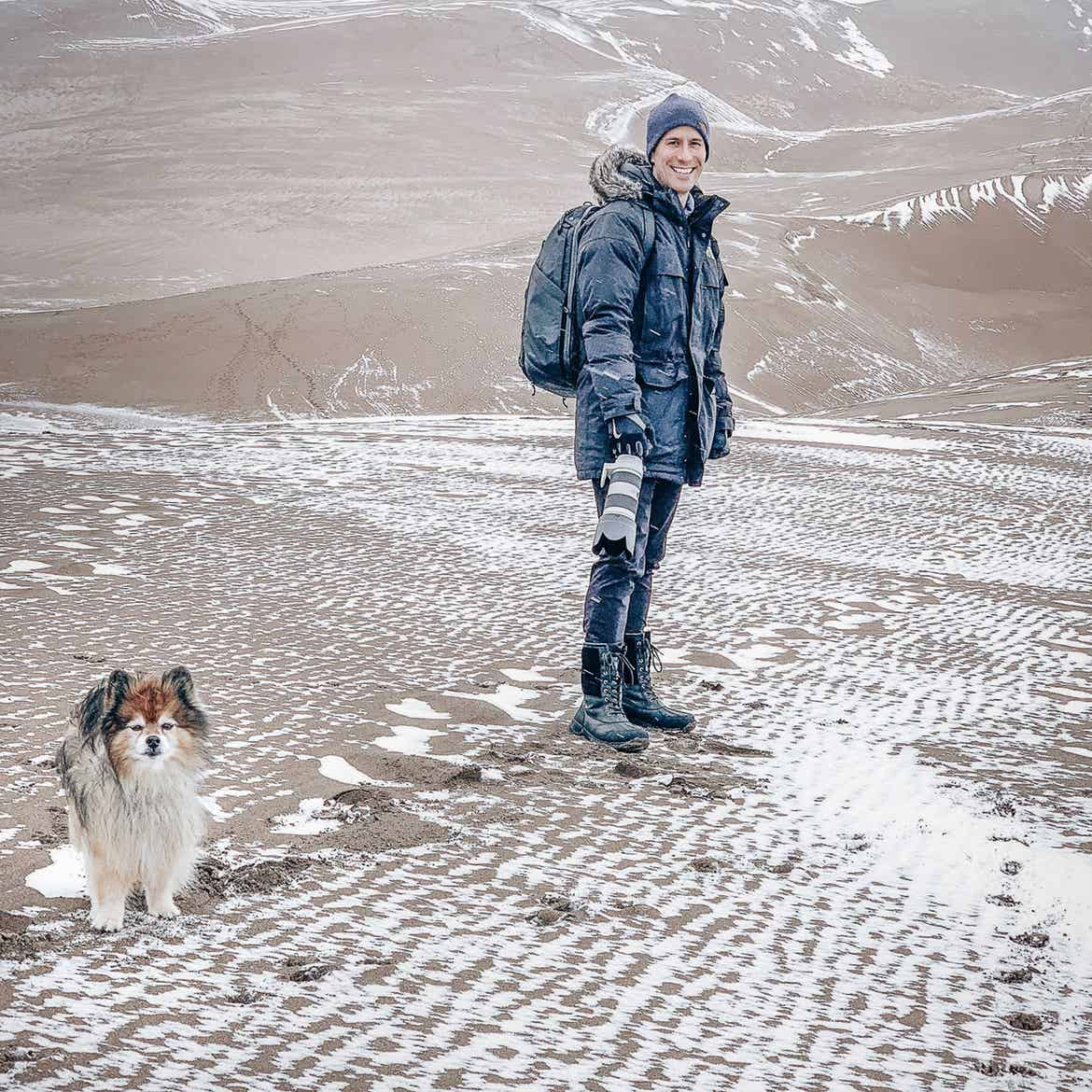 Author, Anthony LeDonne, stand in winter apparel with Bailey the Pomeranian at the Great Sand Dunes National Park and Preserve.