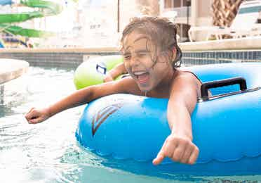 Author, Brenda Rivera Stearns' daughter, Victoria, floating along the lazy river in a blue innertube at our South Beach resort in Myrtle Beach, South Carolina.