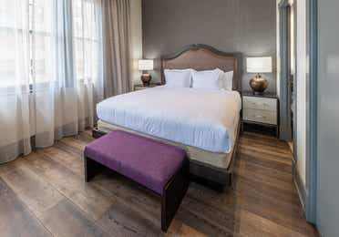 King bed with a purple bedroom bench and three windows in a one-bedroom Signature Collection villa at New Orleans Resort in Louisiana.