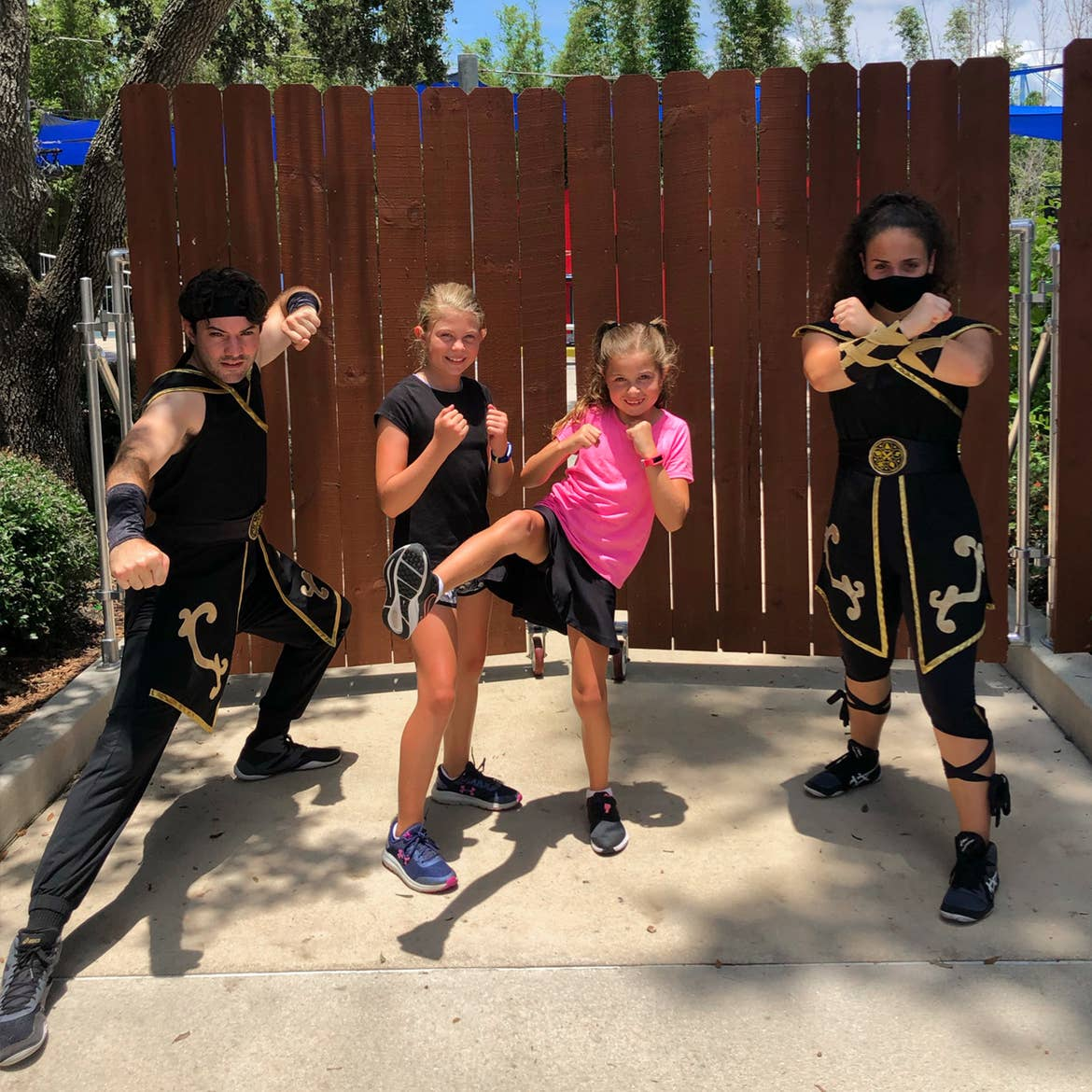 Two young girls (middle) pose with two performers dressed as ninjas.