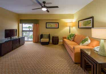 Living room with couch, accent chair, and flat screen TV in West Village at Orange Lake Resort near Orlando, FL