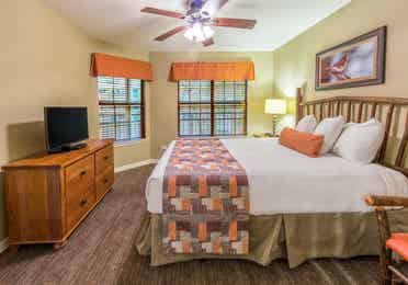 Second bedroom with two windows and a flat screen TV in a two-bedroom villa at Fox River Resort in Sheridan, Illinois