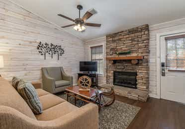 Living room with couch, accent chair, flat screen TV, and fireplace in a two bedroom cabin at Piney Shores Resort in Conroe, Texas