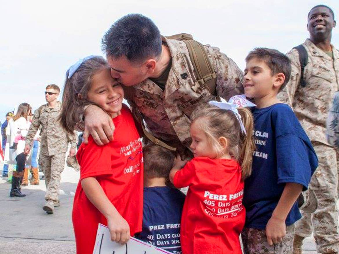 Sara Perezes husband wears his Army uniform as he kisses his daughter at his homecoming from his last deployment.