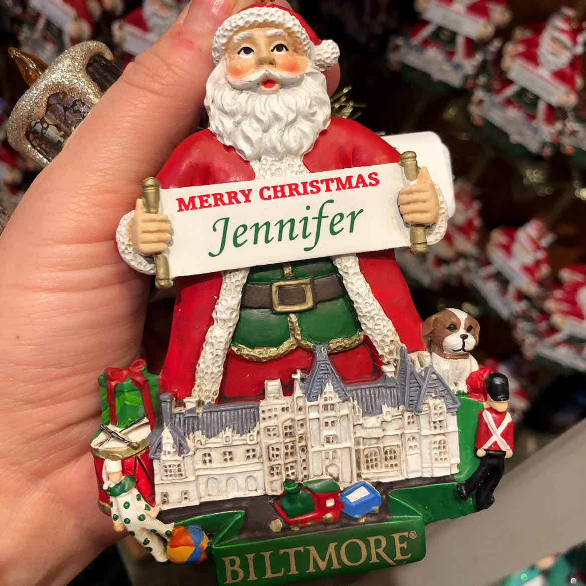 Author, Jenn C. Harmon, holds a Santa Claus ornament which holds a sign that reads, 'Merry Christmas Jennifer' standing behind the silhouette of the Biltmore Estate.