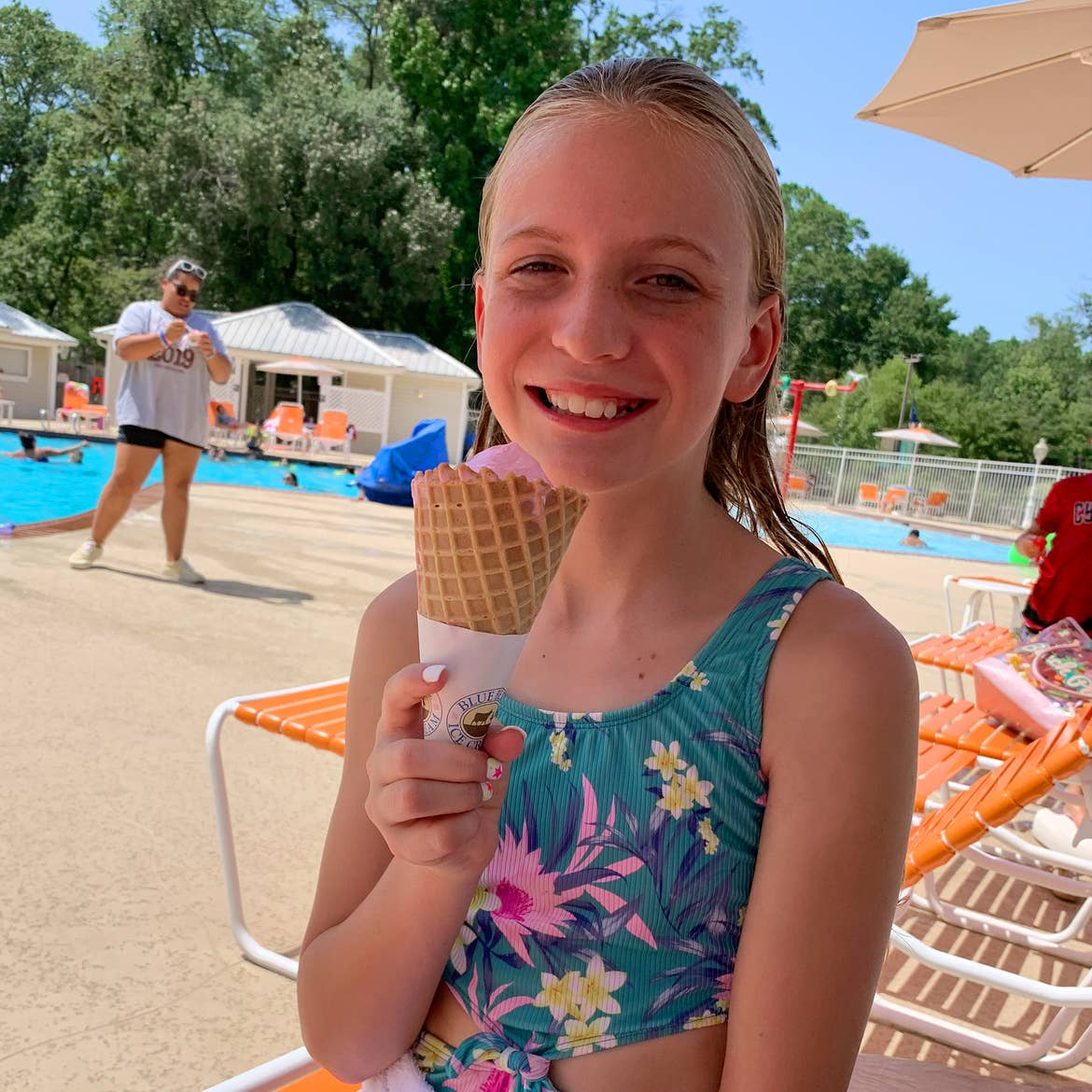 A caucasian girl eats an ice cream cone while wearing a swimsuit near a pool.