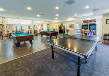 Game room with pool tables, a ping pong table, and arcade games with seating at Fox River Resort in Sheridan, Illinois