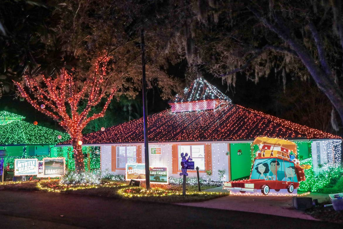 An exterior shot of our HICV villa decorated for the 'Night of a Million Lights' event complete with oversized travel postcards and a family station wagon.