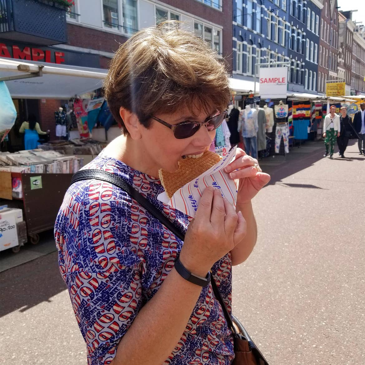 A caucasian woman wearing a patriotic-patterned shirt eats a stroopwaffle in the walkway of the Albert de Cuyp Market in Amsterdam, Netherlands.