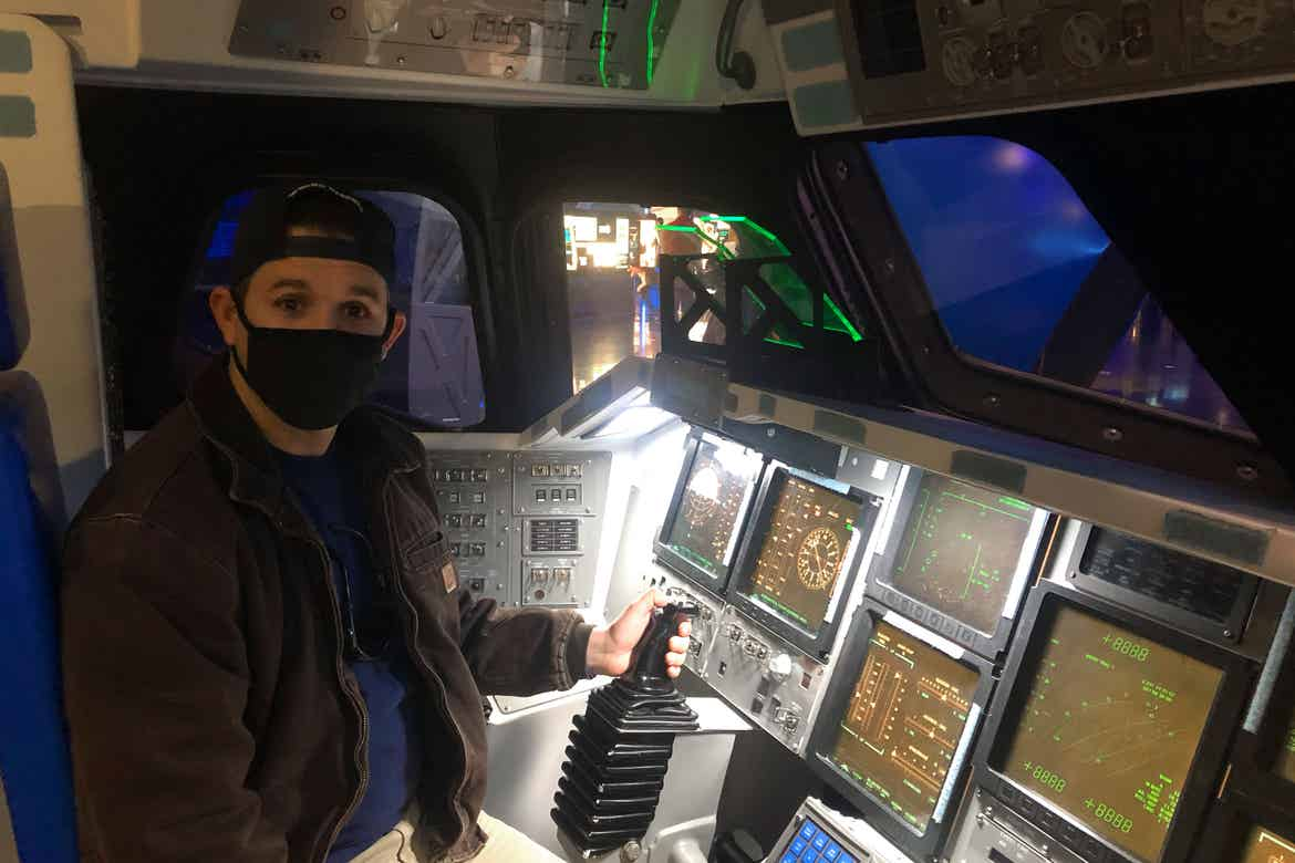 Featured contributor and Checking In Editor, Tori Ferrante's husband, Brooks wearing a mask in the cockpit of an Atlantis rocket simulator at the Kennedy Space Center in Cape Canaveral, Florida.