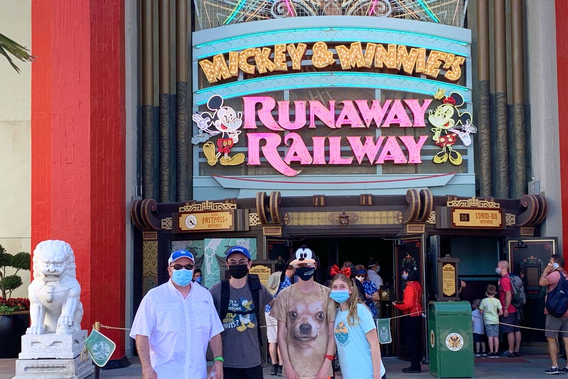 Three men (left) and a young woman (right) stand wearing safety masks outside the ride queue of Mickey & Minnie's Runaway Railway attraction in Disney's Hollywood Studios at Walt Disney World Resort.