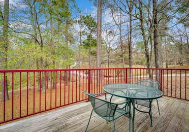 Patio with table and two chairs in a two bedroom cabin at Piney Shores Resort in Conroe, Texas