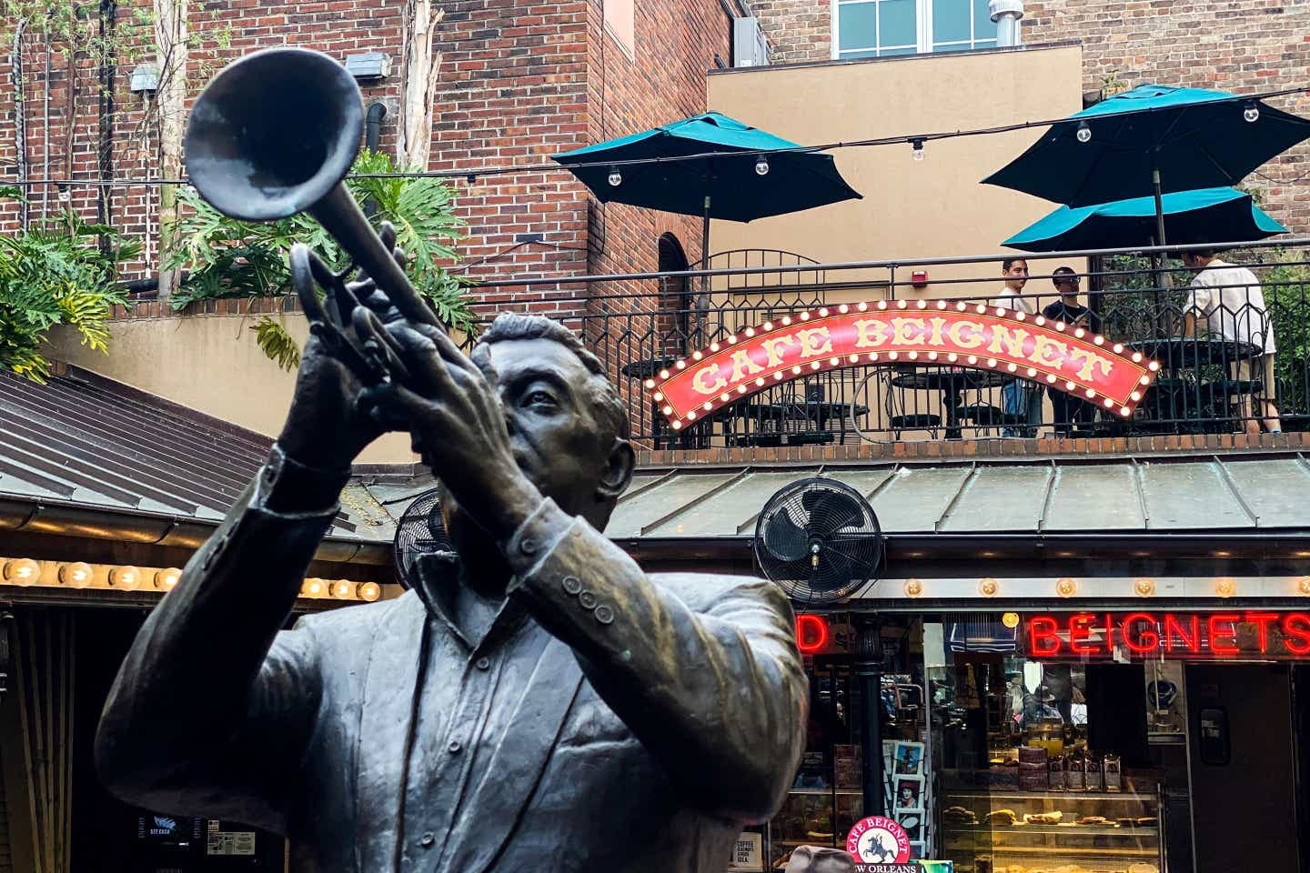 The exterior of Cafe Beignet sign and a bronze statue of a jazz performer.