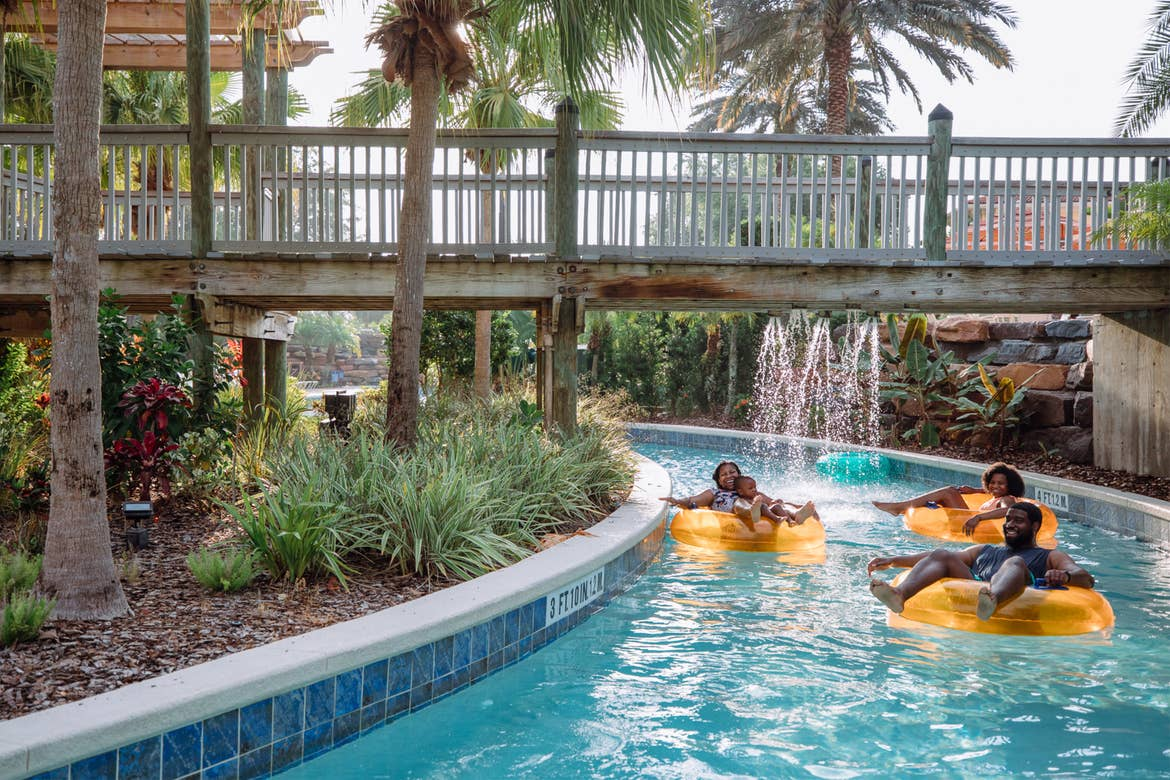 The Godfrey family sits on orange inner tubes in the lazy river in River Island at our Orange Lake resort located in Orlando, FL.