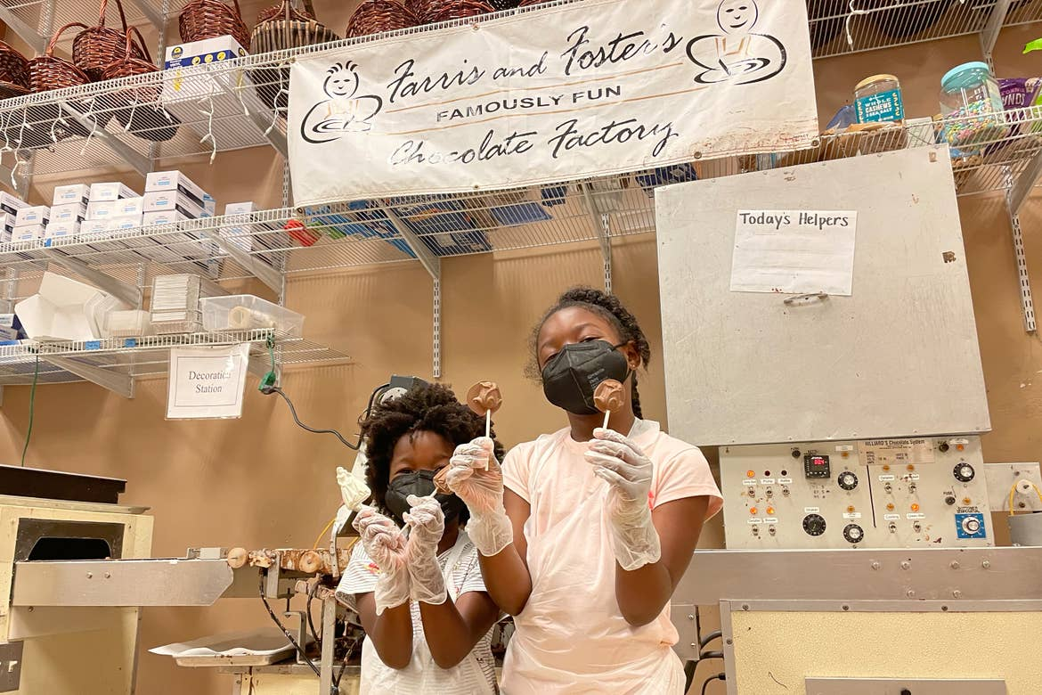 Monet's two daughters, wear safety masks and gloves while they hold sticks of chocolate at Farris and Fosters Chocolate Factory.