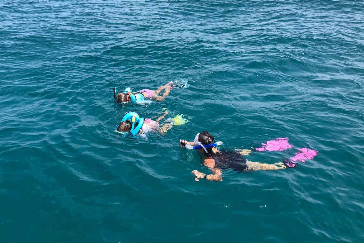 Featured Contributor, Chris Johnston (front-right),and her two daughters, Kyler (back) and Kyndall (middle), wear multi-colored snorkel gear while snorkeling in the ocean.