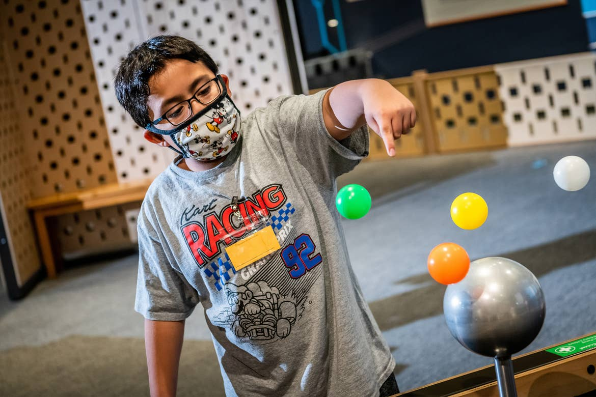A young boy wears a safety mask as he interacts with the Bernouli Table magnetic station at Orlando Science Center.