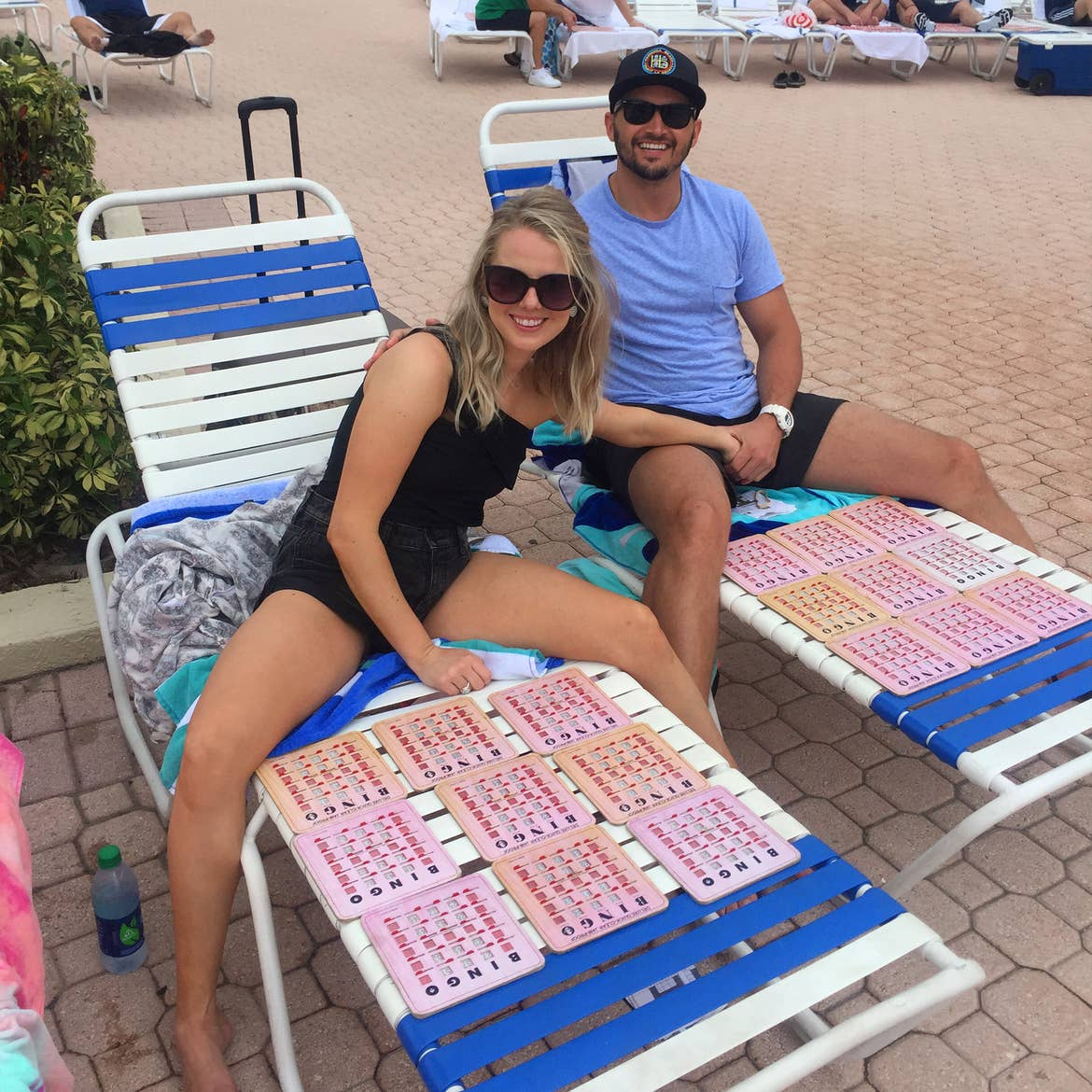 A caucasian woman wearing a black blouse and shorts (left) and Latinx male wearing a blue t-shirt, black shorts and a black hat (right) sit on two lounge chairs with numerous Bingo cards.