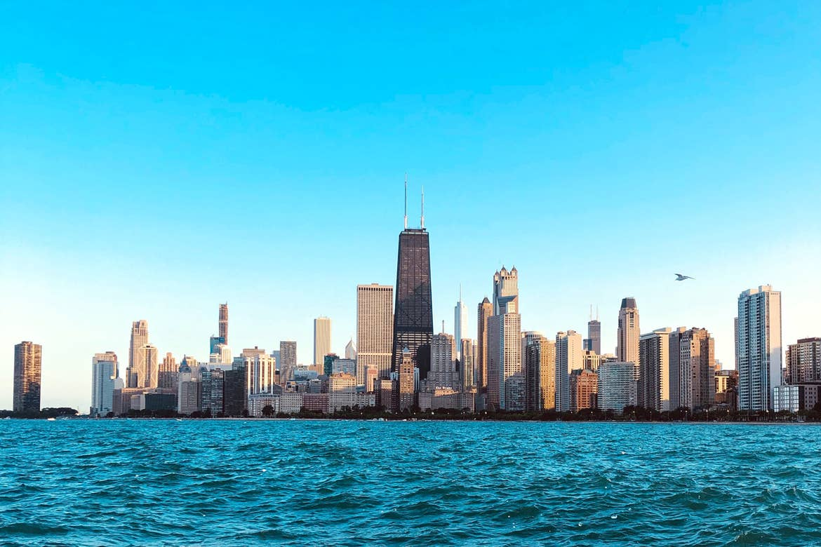 Chicago skyline surrounded by blue skies and blue waters of Lake Michigan.