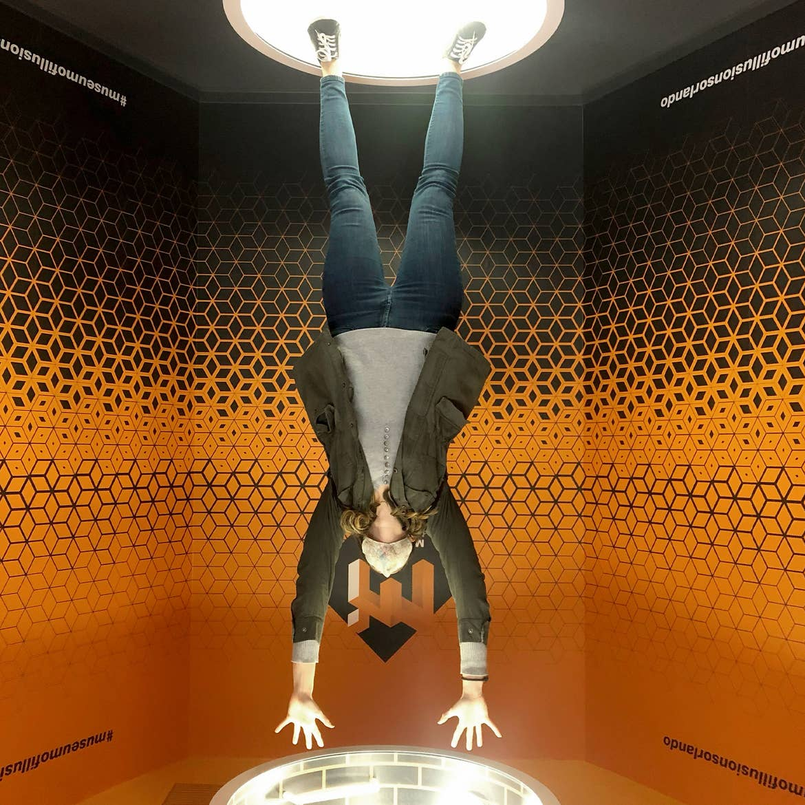 A woman doing what appears to be a handstand at Museum of Illusions at ICON park.