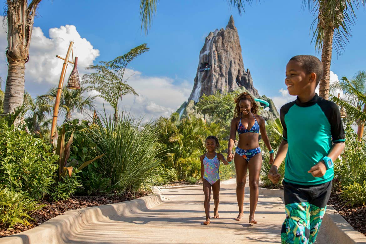 A son, daughter and mother wearing colorful aqua swimwear walk away from Volcano Bay located at Universal Orlando Resort.