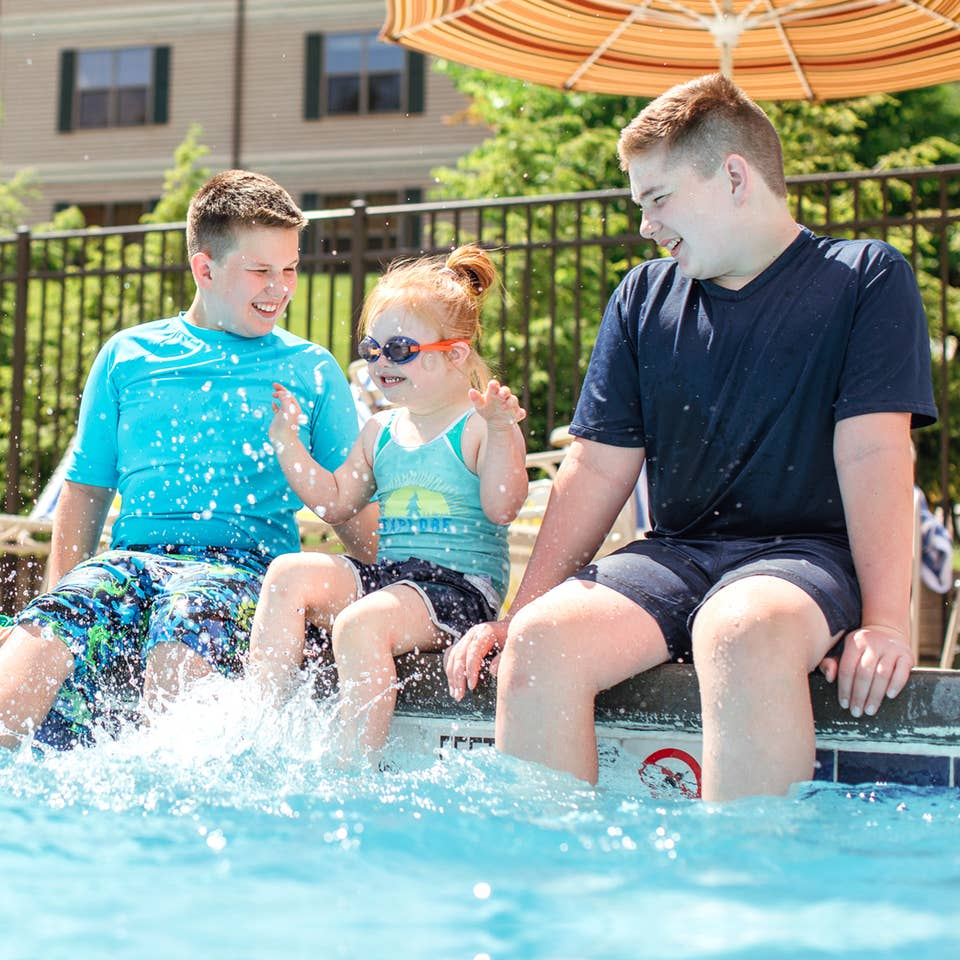 Two young caucasian tween boys (left and right) wearing swim shirts and shorts sit with their feet in a pool with a young caucasian girl (middle) wearing a swimsuit, swimming shorts and goggles as she splashes her feet.