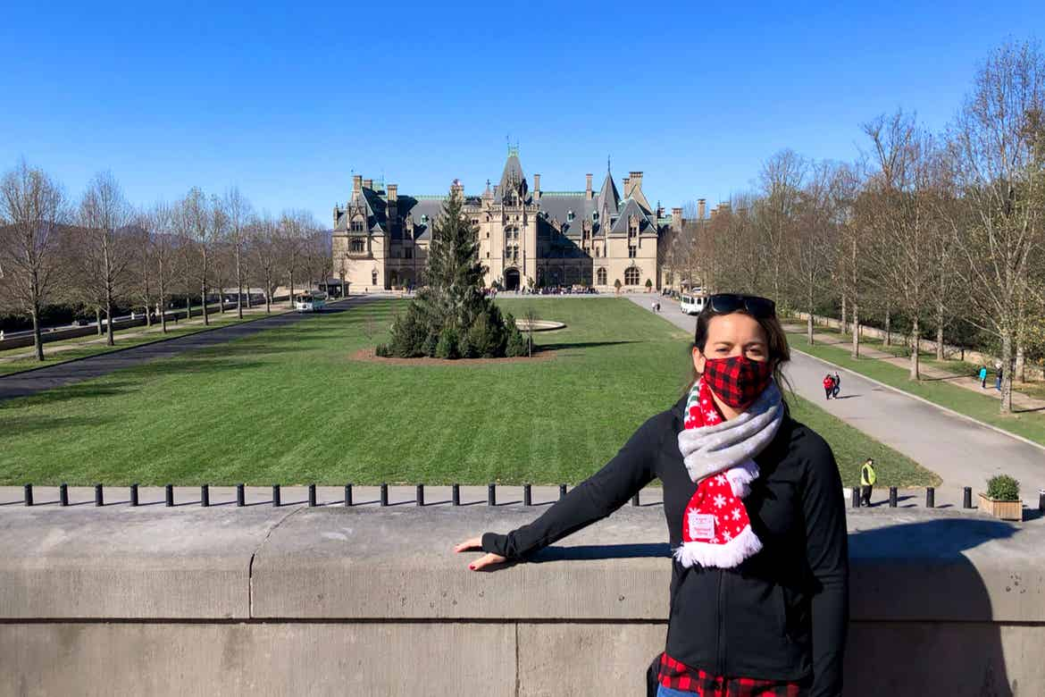 Featured Contributor, Jenn C. Harmon, stands in front of the Biltmore Estate wearing a buffalo plaid red and black face mask and festive scarf over a black jacket.