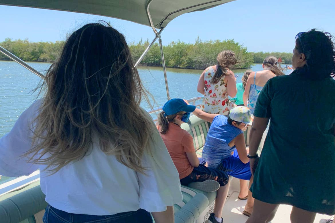 A group of guests sit on a boat during WildeSide Eco Tour.