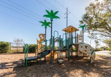 Outdoor playground with palm trees at Orlando Breeze Resort in Florida.