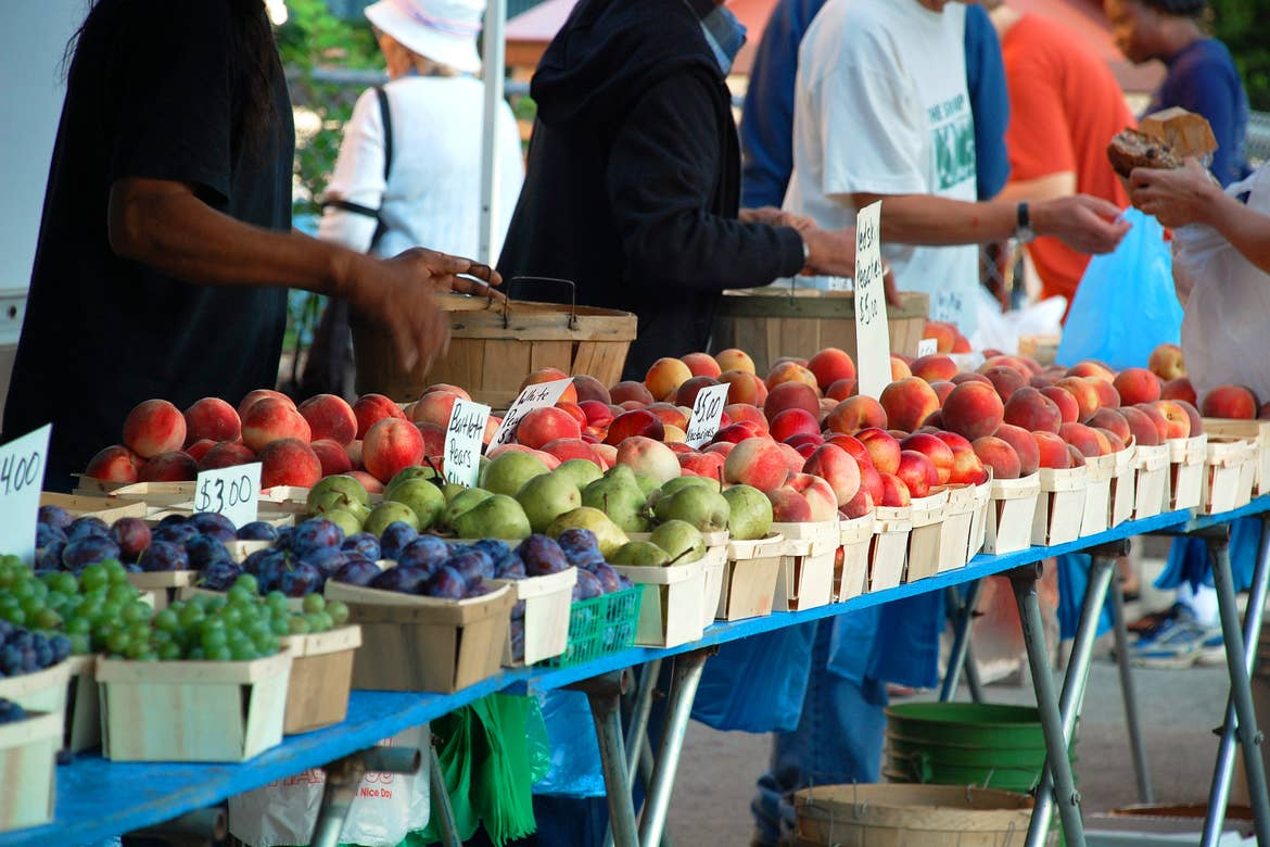 Baskets full of various fruits sit on a table at a farmers market as people approach.