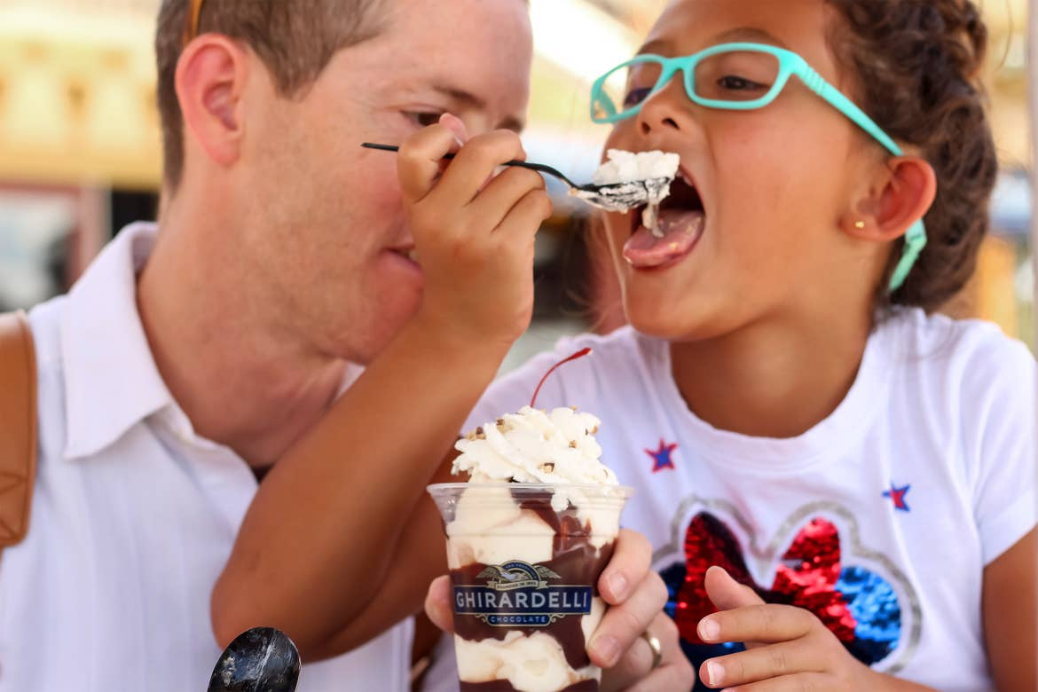 A Caucasian man wearing a white button-up shirt (left) and an Asian girl wearing a sparkly, white Minnie Mouse t-shirt and blue glasses (right) share an ice cream sundae from Ghirardelli Chocolate outdoors.