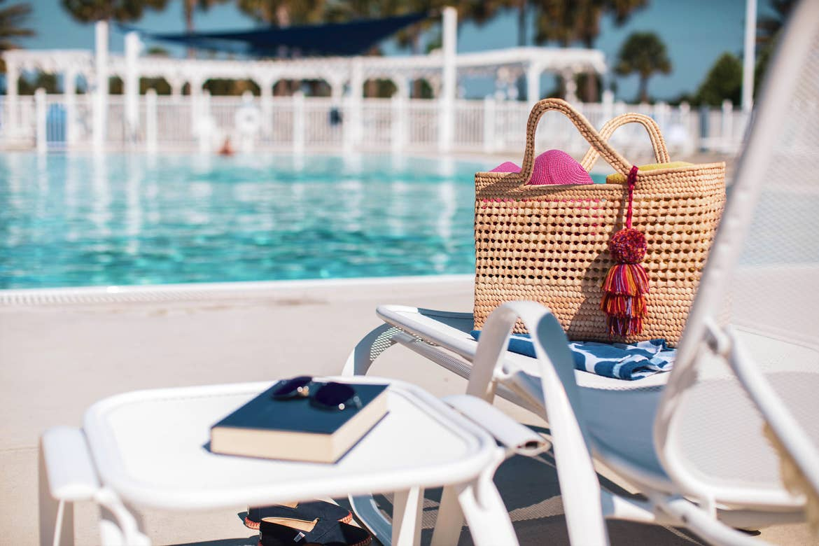 A pool chair lined up at edge of outdoor pool at Orlando Breeze Resort in Florida has a beach bag, towels and a book and sunglasses placed on the chair and table.