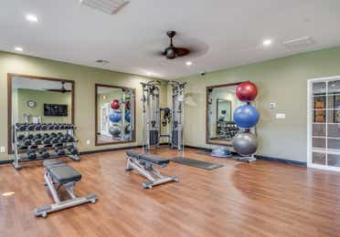 Fitness center with free weights, yoga balls, and yoga mat at Piney Shores Resort in Conroe, Texas