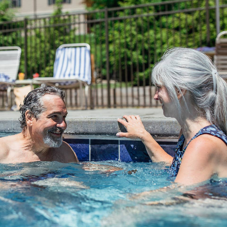 Couple sitting in outdoor pool at Oak n' Spruce Resort in South Lee, Massachusetts.