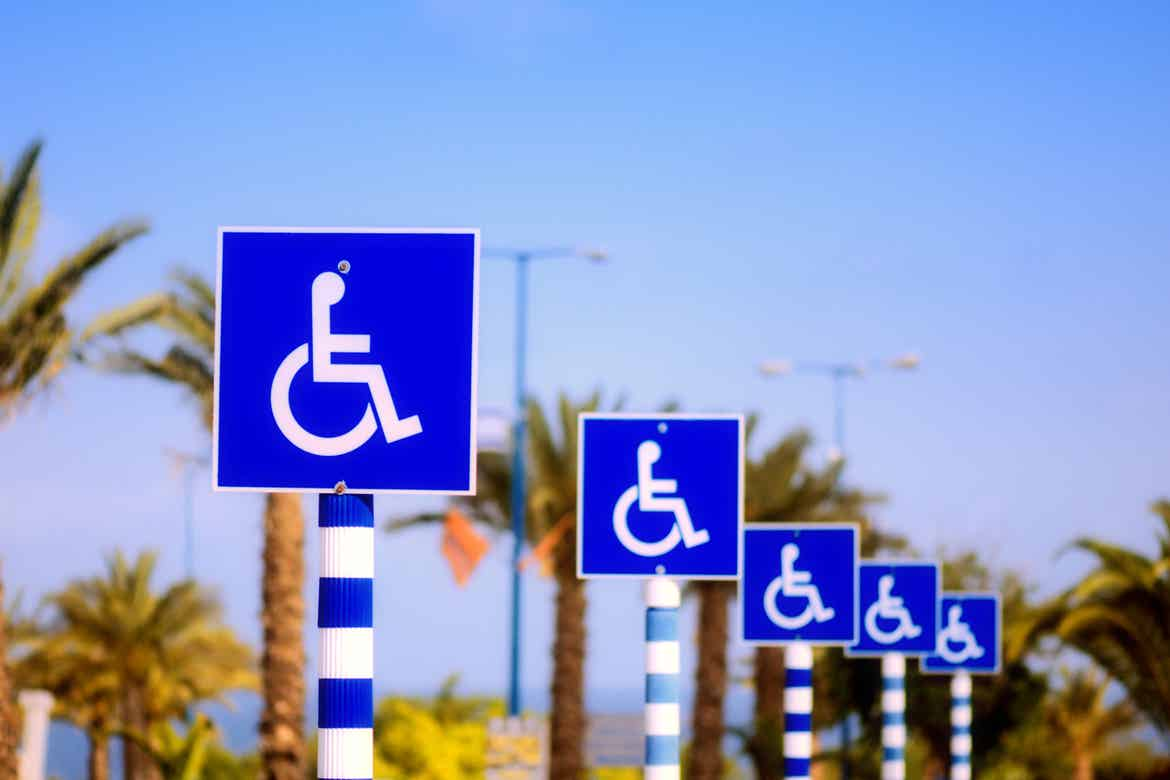 Multiple Wheelchair Parking signs placed near a beachfront.