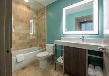 Two bedroom villa bathroom with shower/tub combination, toilet and sink with lighting at New Orleans Resort in Louisiana.