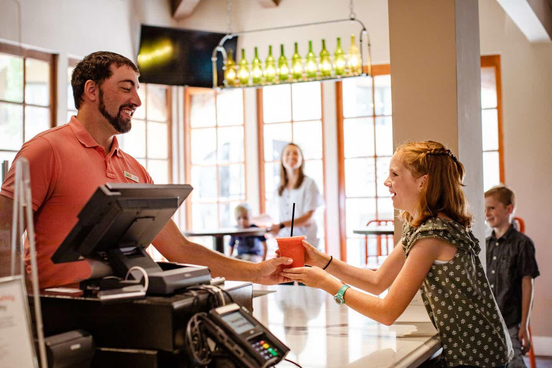 A HICV team member hands over a smoothie to Jessica Averett's daughter.
