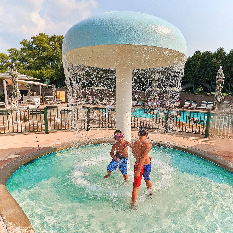 Two boys play under a splash unit in a pool.