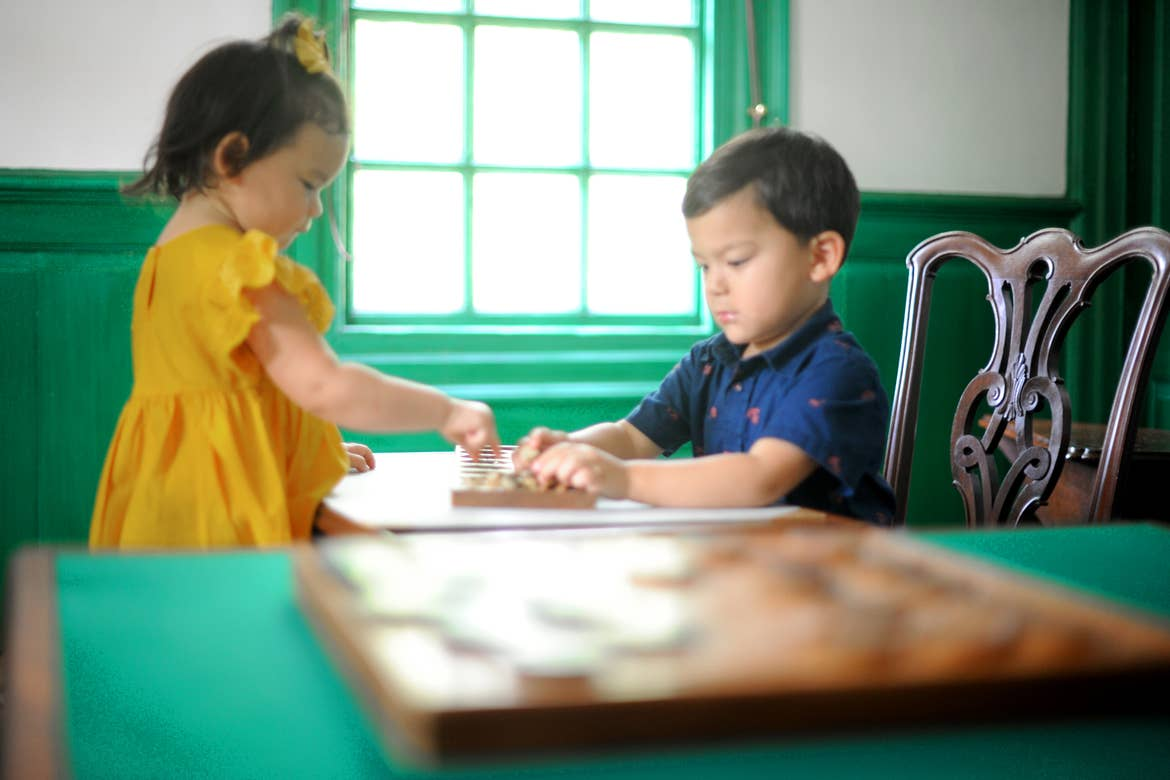 Two Asian Pacific Islander toddlers (left to right: A girl and a boy) sit near a table playing Mancala in a green and white room.