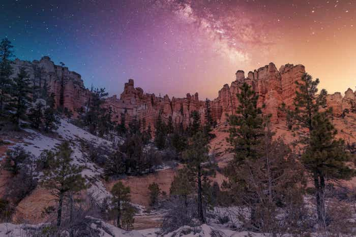 Bryce Canyon National Park night view with colorful sky and bright stars.